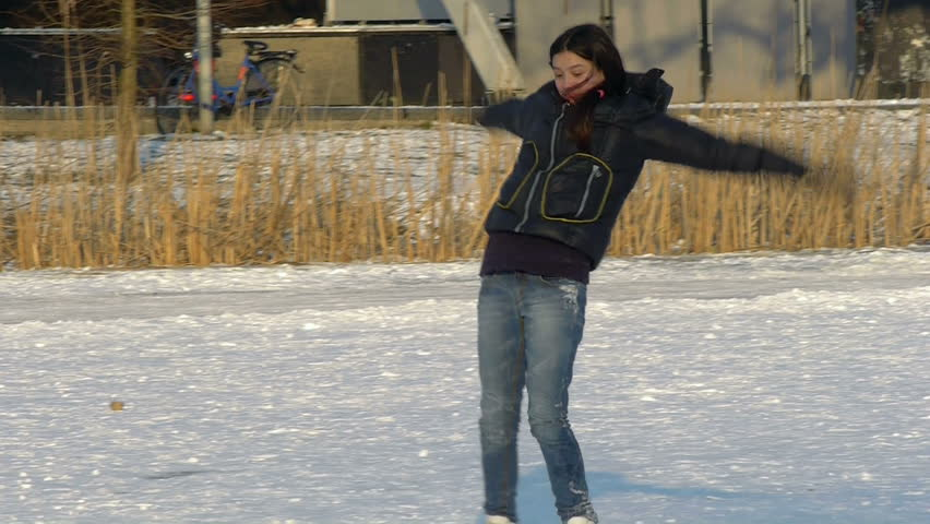 Amsterdam, January 6, 2012. A 12 year old girl runs on natural ice with her skates on and falls, smiles.