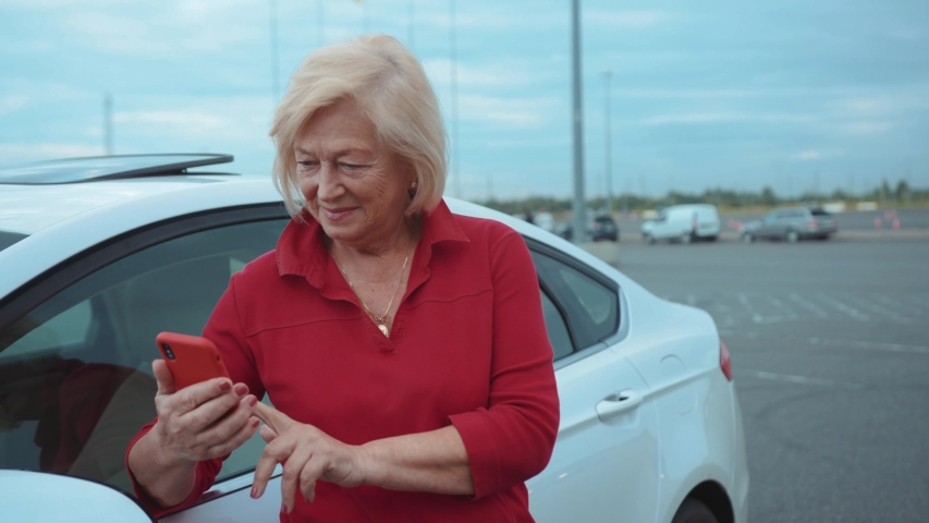 Happy senior woman stand near car use red cell phone smile businesswoman blonde people smartphone cellphone communication internet search lady mobile browse network online slow motion | Shutterstock HD Video #1034924540