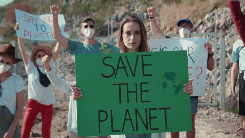 Woman activist portrait holding save the planet green poster at testing field. On background fighting volunteers protesting near garbage mountains. #1034925830