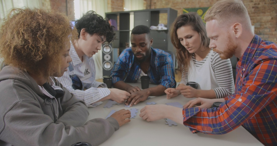 Young multiracial group of hipsters work in team and put parts of puzzle all together during break in modern office | Shutterstock HD Video #1035021650