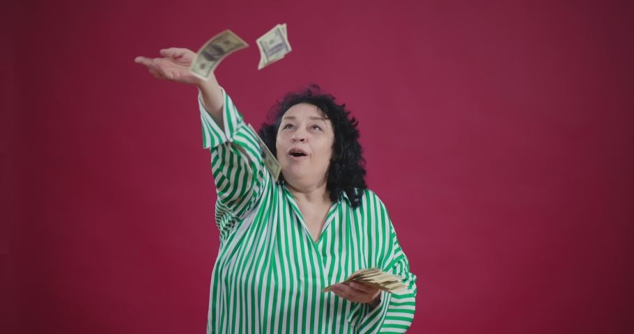 Aged caucasian woman won big amount of money in lottery. She throws banknotes in the air making rain of money, looks overjoyed and full of happiness | Shutterstock HD Video #1035021740