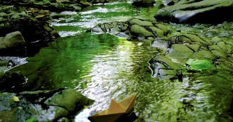 paper boat floating in the fast flowing forest stream. 4K