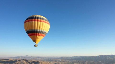 yellow hot air balloon in the blue sky. Hot air balloon over Nevsehir Cappadocia skies. sinematic turkey tourism trip. single hot air balloon in the sky