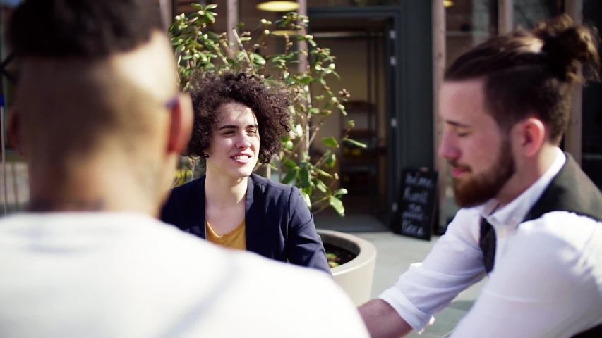 Group of young businesspeople with laptop outdoors in cafe, start-up concept.   Shutterstock HD Video #1035164450
