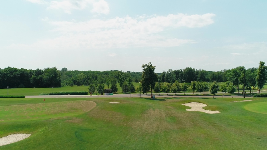 Aerial view of a green golf course with beautiful trees and forest, blue sky with clouds on sunny day in the summer time. 4K drone footage.   Shutterstock HD Video #1035175850