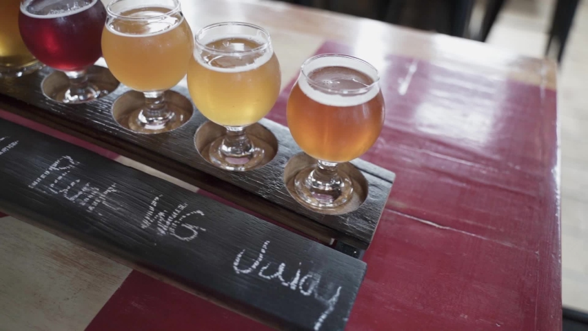 Panning shot seen from aside and up of some different beer tastes on a beer tasting board. | Shutterstock HD Video #1035215750