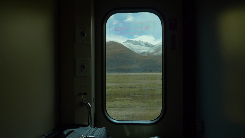 CLOSE UP: Breathtaking view of scenic landscape of Tibet through a small window in the luggage compartment of a sleeper train crossing China. Small window offers a view of snowy Himalaya and plains.