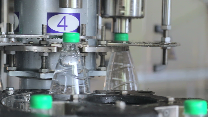 Water bottling line. Automatic feeding of plastic caps and closure | Shutterstock HD Video #1035245030
