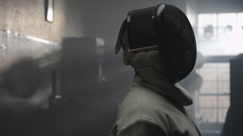 A fencer takes off his fencing mask in a dark and foggy locker room | Shutterstock HD Video #1035247490