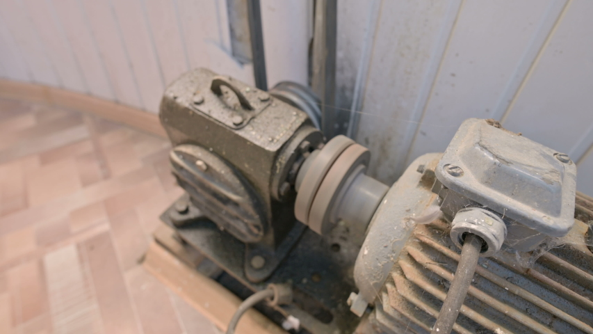 An old electric motor covered with dust and dirt turns a two-thread pulley through a cardan gearbox with a belt drive to another mechanism. The concept of old electro engines and equipment | Shutterstock HD Video #1035294320