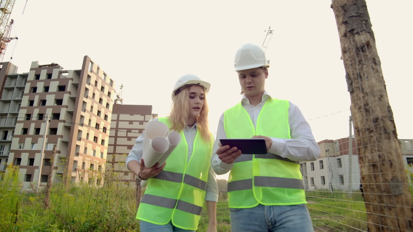 Business, building, industry, technology and people concept - smiling builder in hardhat with tablet pc computer along with woman with drawings of builders at construction site. | Shutterstock HD Video #1035360350