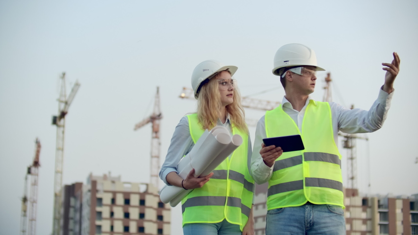 Business, building, industry, technology and people concept - smiling builder in hardhat with tablet pc computer along with woman with drawings of builders at construction site. | Shutterstock HD Video #1035360380