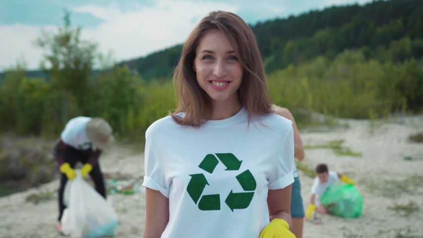 Beautiful portrait of smiling girl having good time cleaning up the beach from litter with friendly eco team. Charity cleaning up operation. | Shutterstock HD Video #1035365390