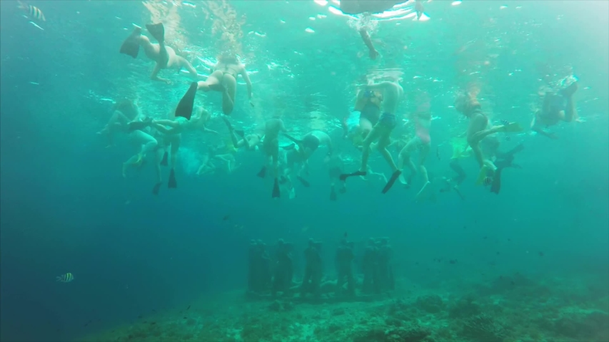 Slow motion underwater view of old statues on the sea floor and many tourists snorkling to explore them. Clean balinese water, Indonesia   Shutterstock HD Video #1035417290