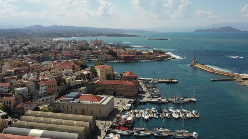 Aerial drone view video of iconic and picturesque Venetian old port of Chania with famous lighthouse and traditional character, Crete island, Greece. Architecture of the Venetian port in Chania. | Shutterstock HD Video #1035430520