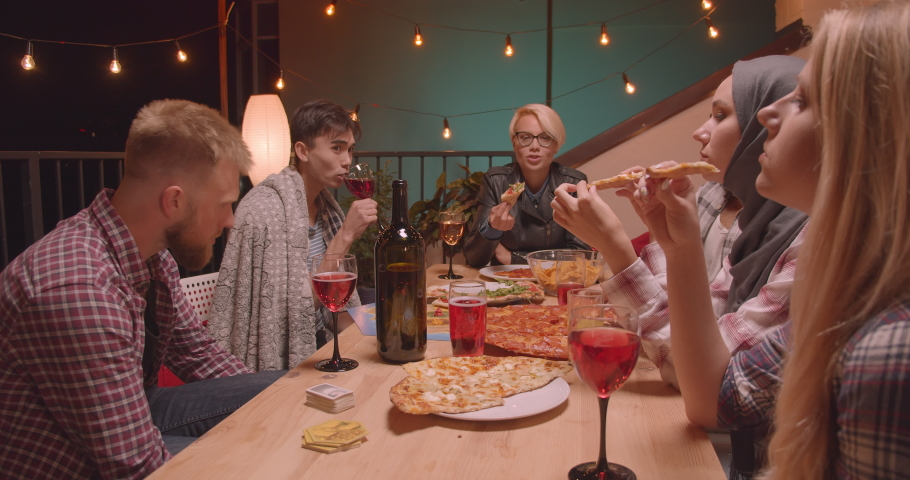 Closeup portrait of diverse multiracial group of friends eating pizza celebrating at cool party in cozy evening with fairy lights on background #1035467120