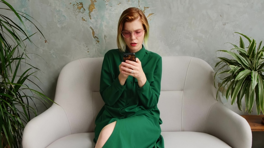 A young woman uses a mobile phone, texting and playing mobile games. Modern loft ecological interior. Green. | Shutterstock HD Video #1035479060