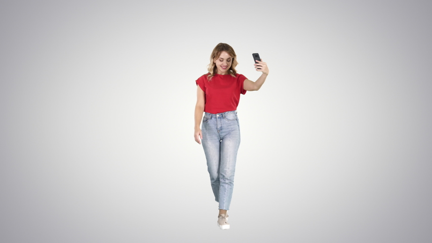 Cheerful young hipster girl streaming video for internet blog while walking on gradient background. | Shutterstock HD Video #1035489080
