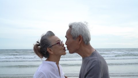 Asian couple senior elder retire resting relax kissing and hugging sunset beach honeymoon family together happiness people lifestyle, Slow motion footage
