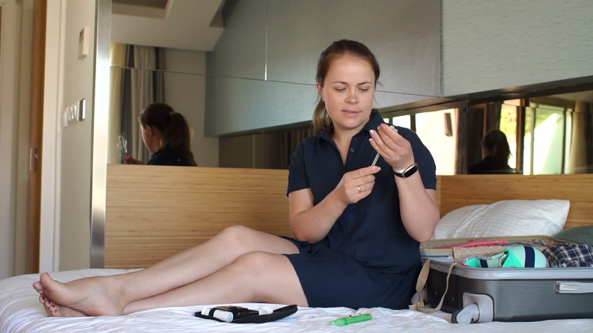A young diabetic woman is injecting herself with insulin in a hotel sitting on a bed next to a suitcase and clothes. The woman was a diabetic traveling. Diabetic injections of insulin during the trip. | Shutterstock HD Video #1035515720