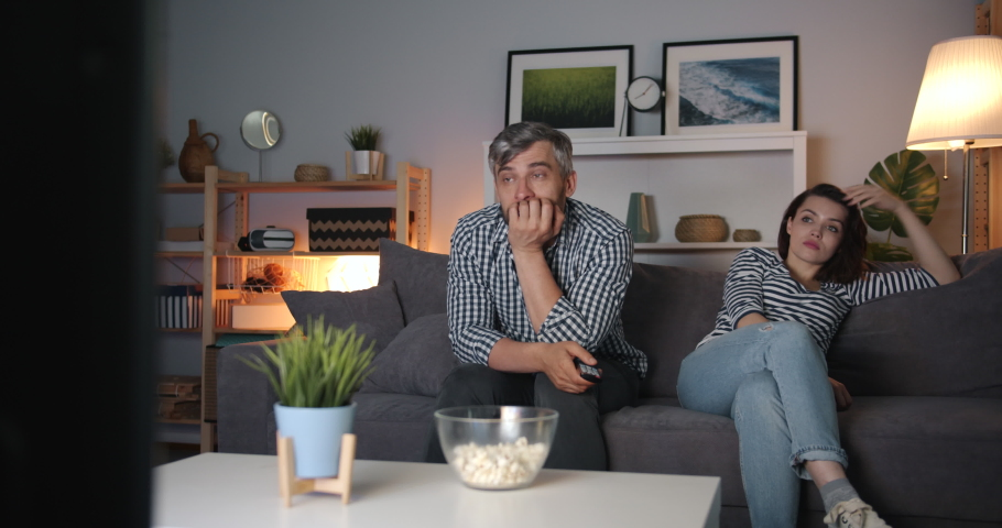 Girl and guy beautiful middle-aged couple are watching TV at night with sad faces, guy is wiping eyes with tissue. Human emotions and television concept. | Shutterstock HD Video #1035520460