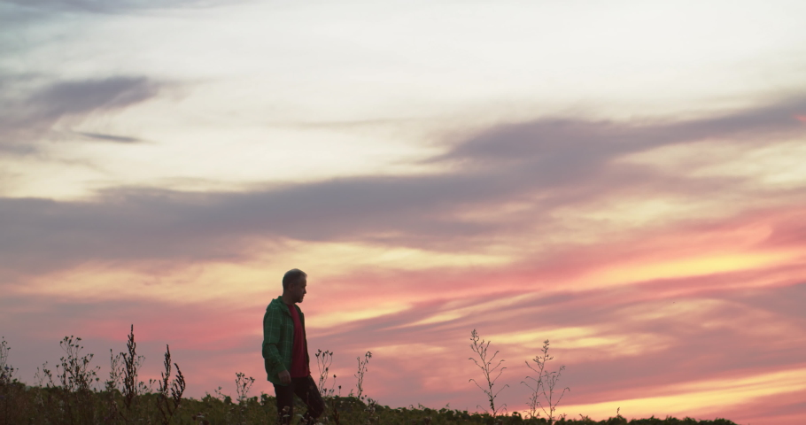 Peaceful man walking in rural farmland in colorful pink sunset with wind turbines spinning advanced technology electricity production.   Shutterstock HD Video #1035557600