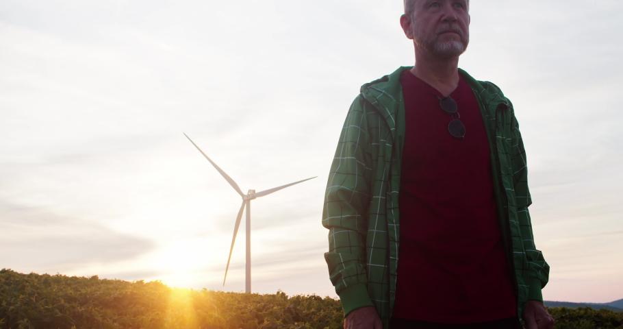 Outdoor portrait elderly farmer walking in greenland meadows with windmills spinning generating power under sunset sky. Renewable energy production.   Shutterstock HD Video #1035557630