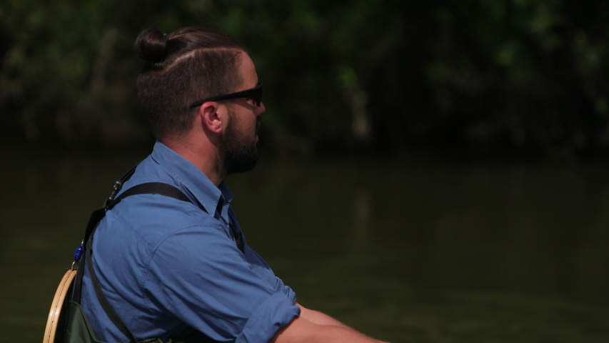 Male fisherman with a beard and dark hair in special clothes, glasses, throws a float, a man fishing on the river, standing in the water, a small current, the nature is beautiful, summer, close-up   Shutterstock HD Video #1035563810