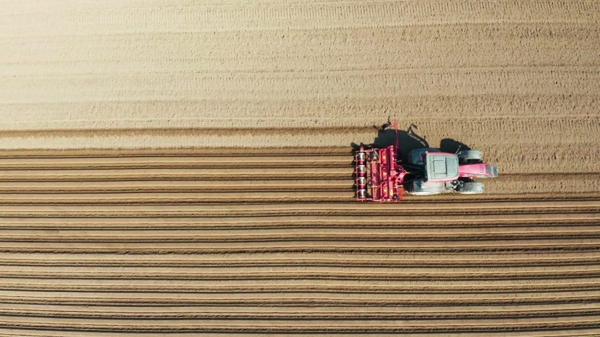 Aerial view tractor cuts furrows in farm field for sowing farm tractor with rotary harrow plow preparing land for sowing. Tractor with harrows prepares the agricultural land for planting crop | Shutterstock HD Video #1035570080