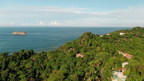 Drone Footage of Green Tropical Peninsula Near Manuel Antonio Finca, Costa Rica Panning Left to the Pacific Ocean with Small Rocky Islands in the Distance on a Sunny and Partly Cloudy Day