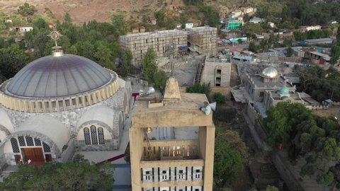 Rotating drone shot flying around bell tower with cross and Ethiopian Orthodox church in Aksum, Christian religion and culture in Ethiopia Africa