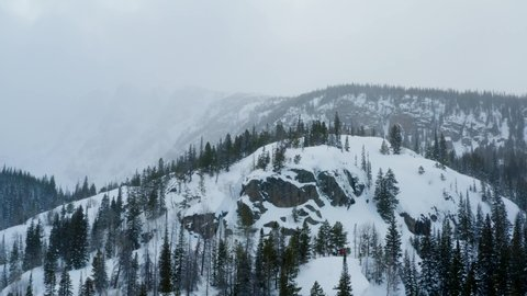 An aerial drone shoting backwards while slowly panning sideways overlooking foggy mountains with trees covered in snow during the winter.