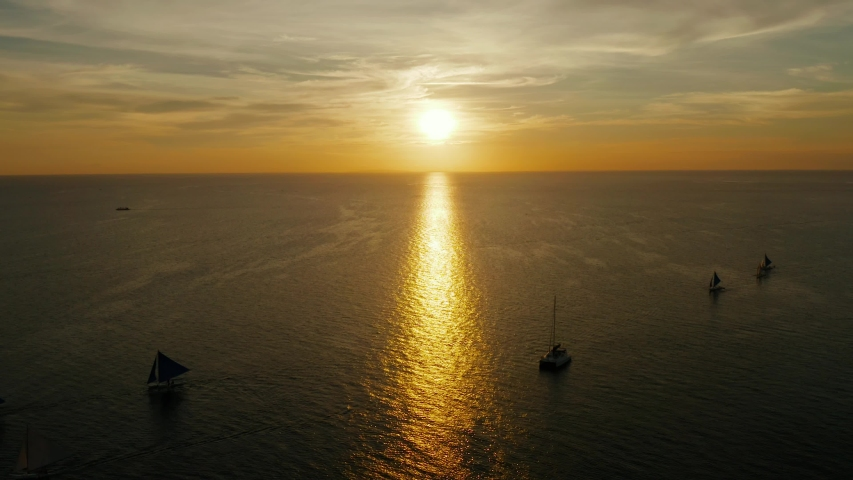 Sunset above the sea surface with waves, aerial view Boracay, Philippines. Reflected sun on a water surface. Sunset over ocean. Seascape, Summer and travel vacation concept | Shutterstock HD Video #1035833240