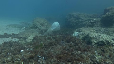 Plastic pollution, a lot plastic garbage on sea bottom covered with algae. Slow motion. Plastic bottles, bags and dishes on the seabed in Mediterranean Sea, Europe.