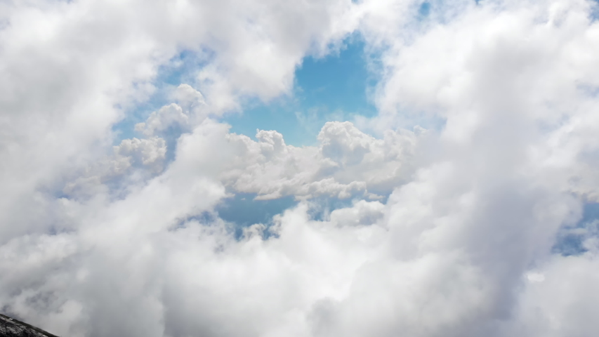 Flying through amazingly beautiful cloudscape. Picturesque timelapse of white fluffy clouds moving softly on the clear blue sky. Direct view from the cockpit.