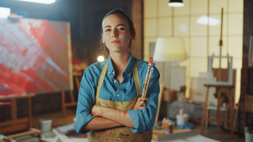 Talented Young Female Artist Dirty with Paint, Wearing Apron, Crosses Arms while Holding Brushes, Looks at the Camera with a Smile. Authentic Creative Studio with Large Canvas. Face Portrait | Shutterstock HD Video #1036107680