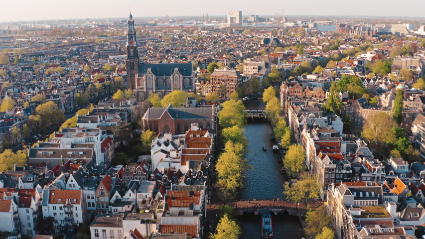 Amsterdam, Netherlands: drone view of Westerkerk church and narrow canal with bridges and boats traffic | Shutterstock HD Video #1036155410