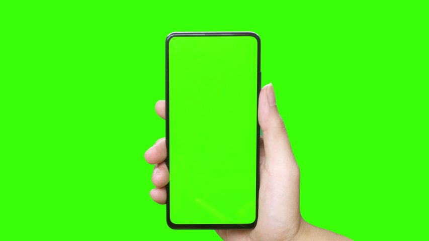 Man's hand holding a mobile telephone with a vertical green screen in tram chroma key smartphone technology cell phone touch message display hand with luma white and black key | Shutterstock HD Video #1036222220