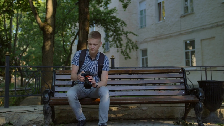 Young guy tourist sits in an alley on a bench and scrolls at the photographs taken on a digital expensive big photo camera. Casual clothes with a black backpack. Middle shot | Shutterstock HD Video #1036277360