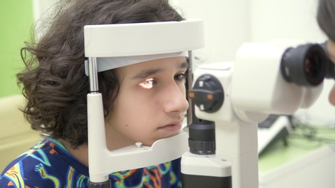 Ophthalmology concept, optometry. Medical ophthalmic device for eye examination. a teenager boy checks his eyesight at a doctor appointment, on equipment.