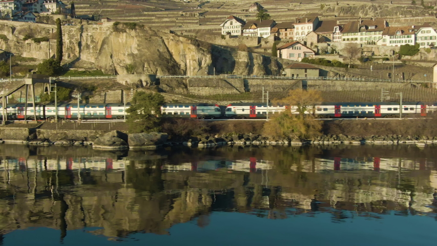 Double-Decker Passenger Train Goes Along Lake Geneva Shore. Reflection in Water. Terraced Vineyards of Lavaux and Village. Switzerland. Aerial Low-Level Shot. Drone Flies Sideways | Shutterstock HD Video #1036347920