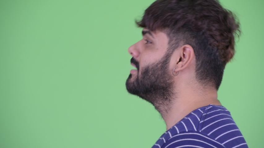 Closeup profile view of happy young overweight bearded Indian man talking | Shutterstock HD Video #1036384520
