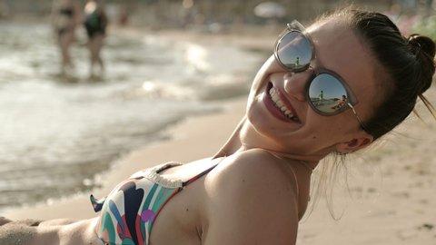 Woman sunbathing on the beach showing legs with bikini beach body and beautiful healthy skin. Female model on vacation. Beach travel people