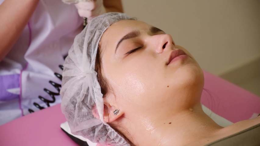 Cosmetology beauty clinic.Professional cosmetologist conducts cell oxygenation for the face Ozone treatment with cosmetology apparat. Physiotheraphy. Lifting effect .  | Shutterstock HD Video #1036506350