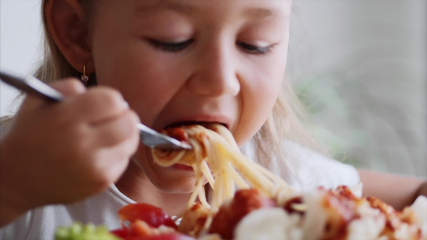 Close up portrait of a child girl eats spaghetti with salad, tomatoes, broccoli and red sauce in a light domestic room. A small child is twisting spaghetti on a fork and eating meal.  | Shutterstock HD Video #1036525400