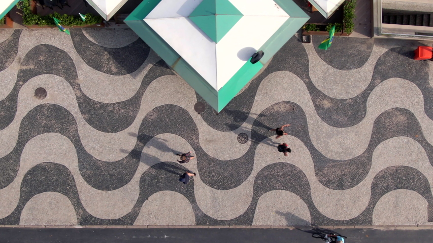 Top-down aerial view of people walking on the iconic Copacabana Beach mosaic sidewalk in Rio de Janeiro, Brazil. | Shutterstock HD Video #1036530080