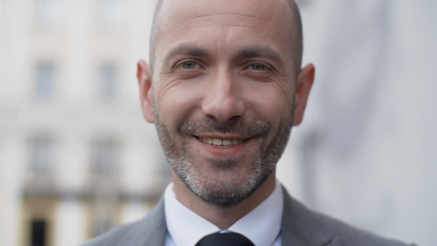 Close up attractive middle aged bearded man in business suit in a good mood looking into camera and smiling in the city outdoors. Portrait of handsome male businessman standing on office porch #1036604150