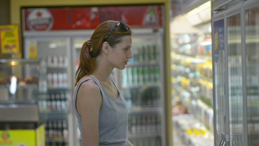 Young beautiful woman choosing mineral water in supermarket while Asia travel. Side of redhead female opening fridge door and taking cool bottles in hand in grocery store. Lady traveler wearing casual | Shutterstock HD Video #1036719230