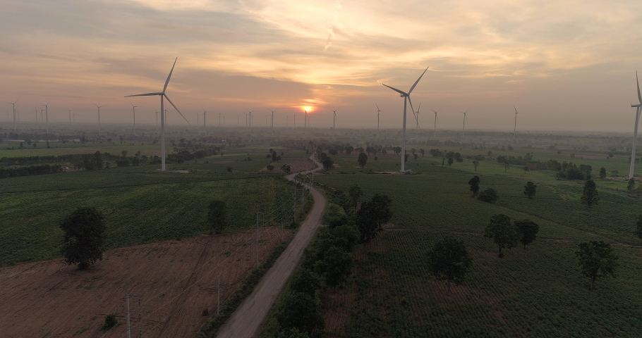 Aerial view of Wind turbines Energy Production- 4k aerial shot on sunset. 4k drone footage turbines at sunrise with clouds | Shutterstock HD Video #1036853720