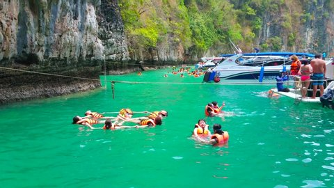 PHIPHI LEH, THAILAND - APRIL 27, 2019: The group of tourists performs the figures of synchronized swimming in Pileh Bay lagoon of Phi Phi Leh Island, on April 27 in PhiPhi Leh
